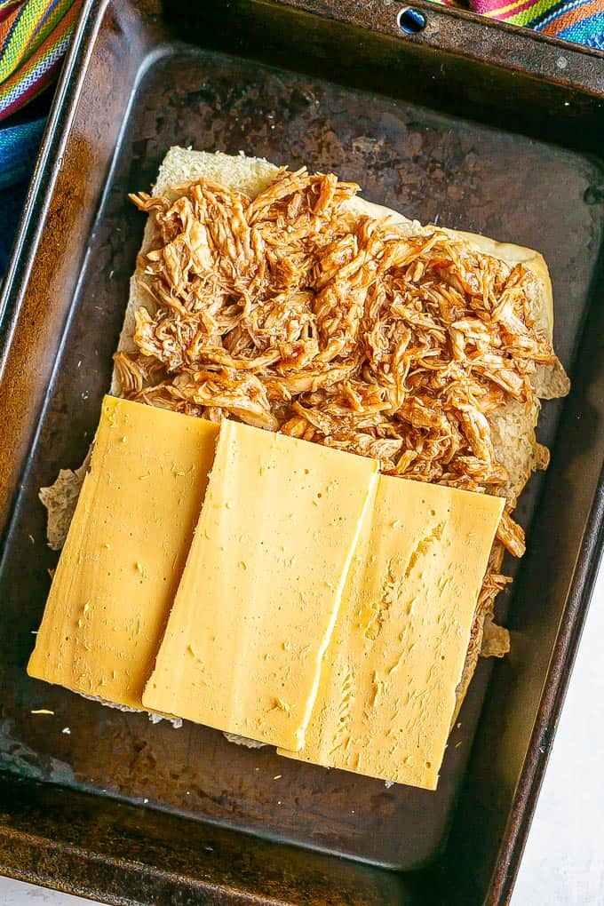 The bottom half of a tray of slider rolls topped with BBQ shredded chicken and sliced American cheese before being baked