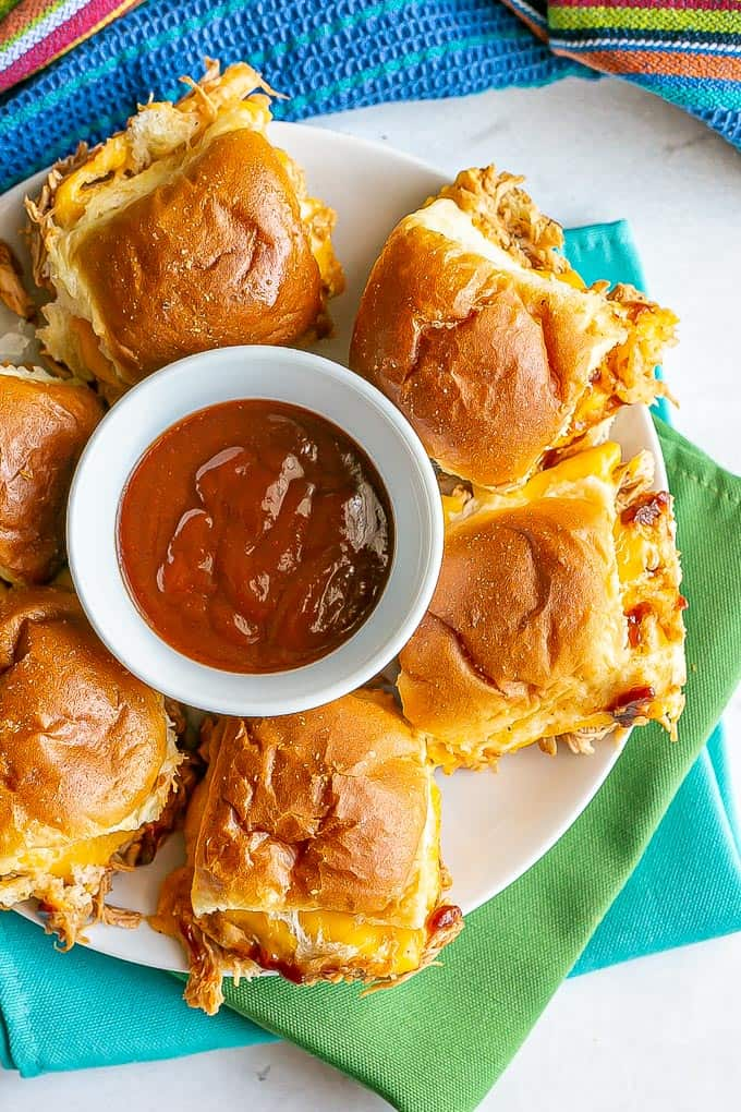 Baked BBQ chicken sliders with cheese served on a white plate with a bowl of BBQ sauce for dipping