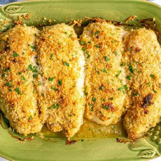 Crispy browned baked cheesy chicken breasts in a green casserole dish after cooking