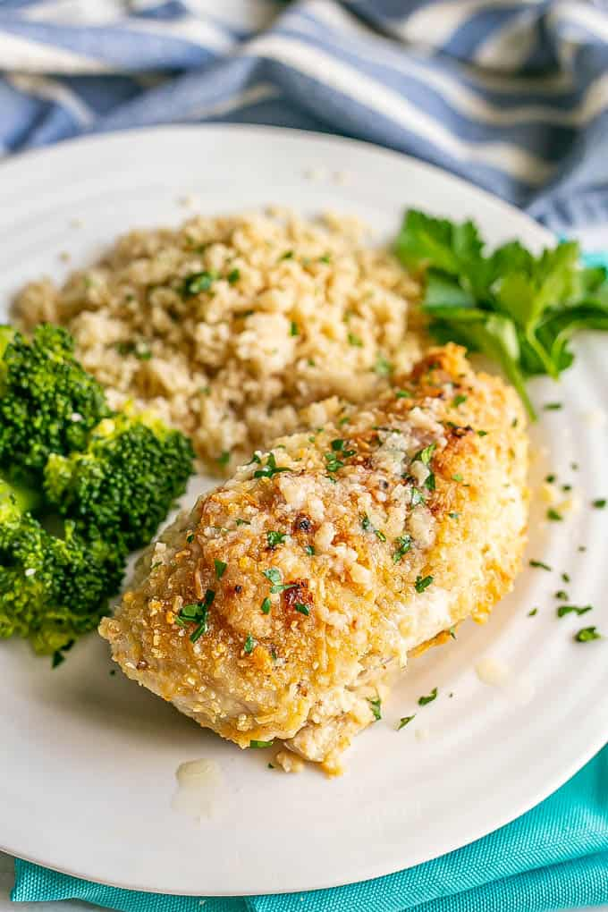A cheesy chicken breast served on a white dinner plate with rice and broccoli