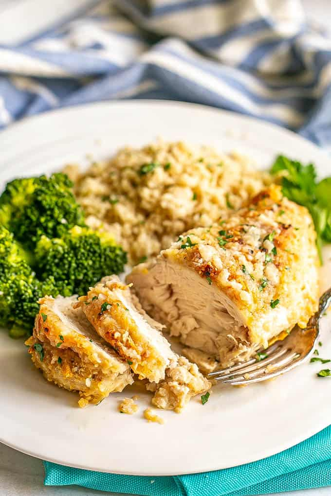 A sliced, breaded cheesy chicken breast served on a white dinner plate with rice and broccoli