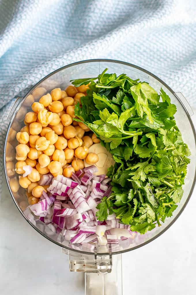 Chickpeas, fresh herbs and red onion in a food processor before being broken down