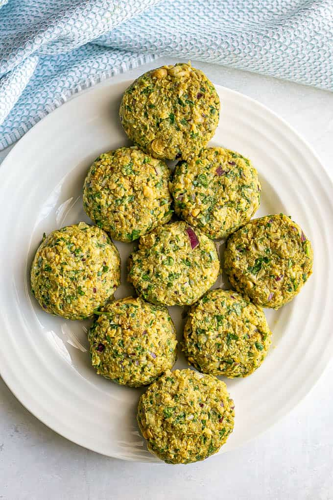 Falafel patties on a white plate before being cooked