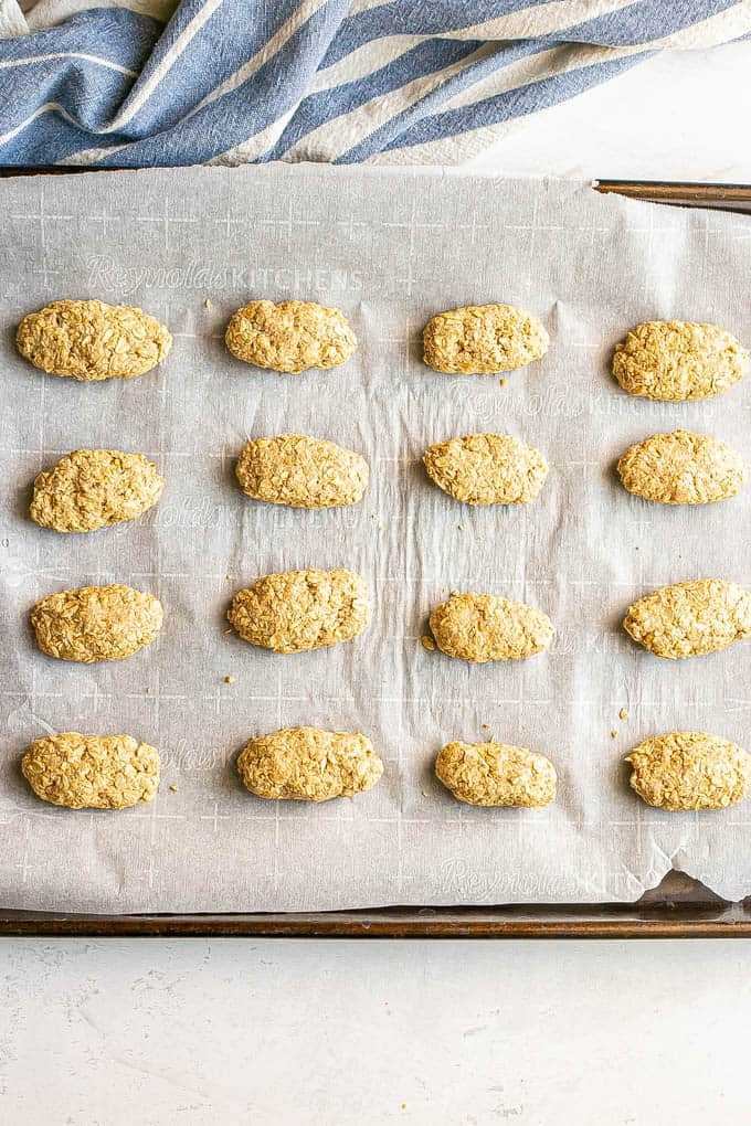 Parchment paper lined baking sheet with a dozen individual teething biscuits before being baked