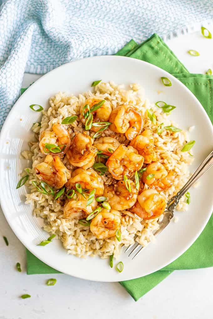 Overhead shot of sauteed honey garlic shrimp over rice on a white plate with green onions sprinkled over