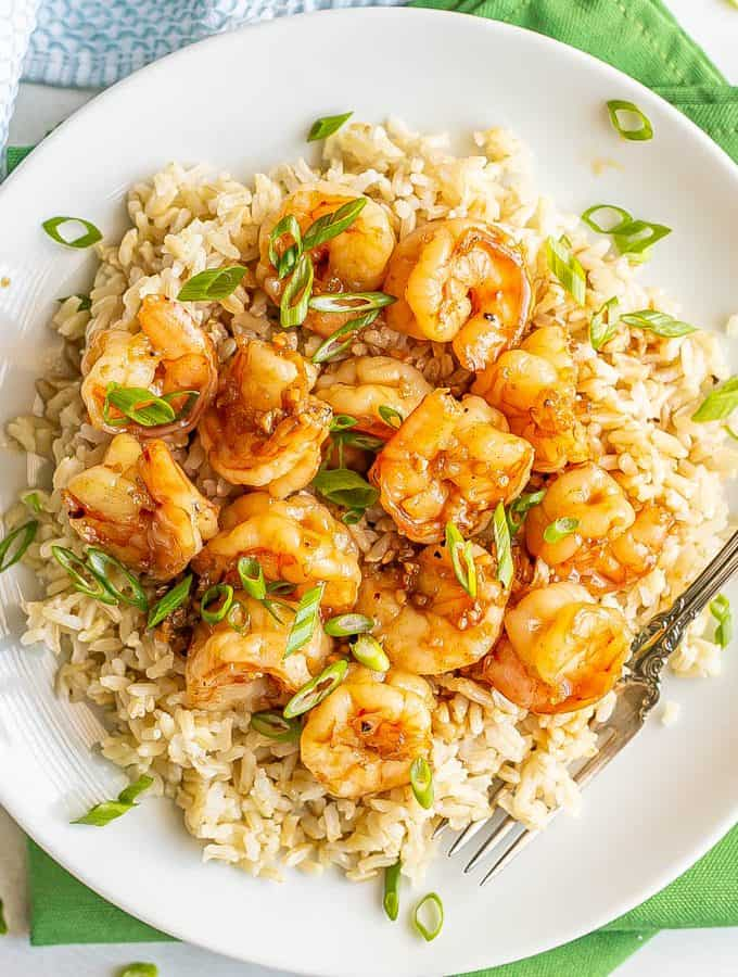 Honey garlic shrimp piled over some steamed brown rice on a white plate, topped with sliced green onions