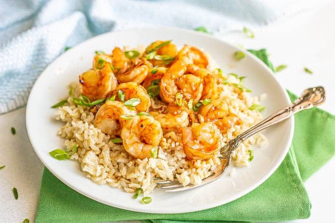Honey garlic shrimp piled over some steamed rice on a white plate, topped with sliced green onions with a fork resting on the plate