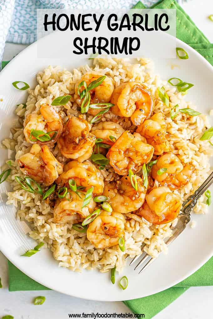 Honey garlic shrimp piled over some steamed brown rice on a white plate, topped with sliced green onions with a text overlay on the photo