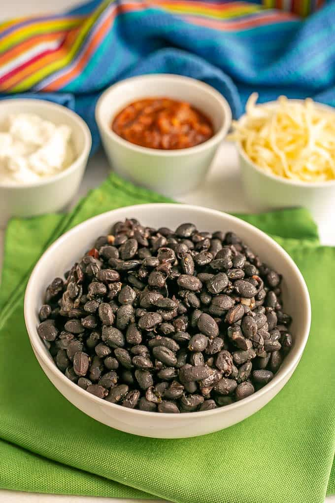 A white bowl of cooked black beans on top of green napkins with bowls of toppings in the background