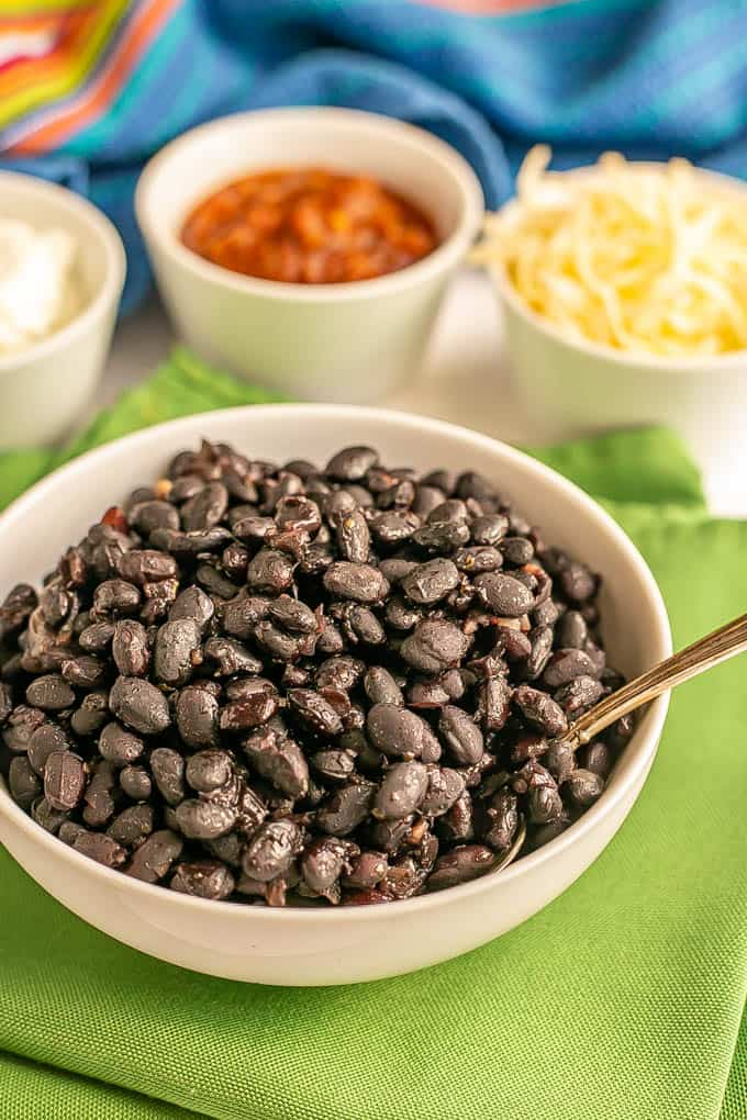 A white bowl of cooked black beans with a spoon resting in it and bowls of toppings in the background