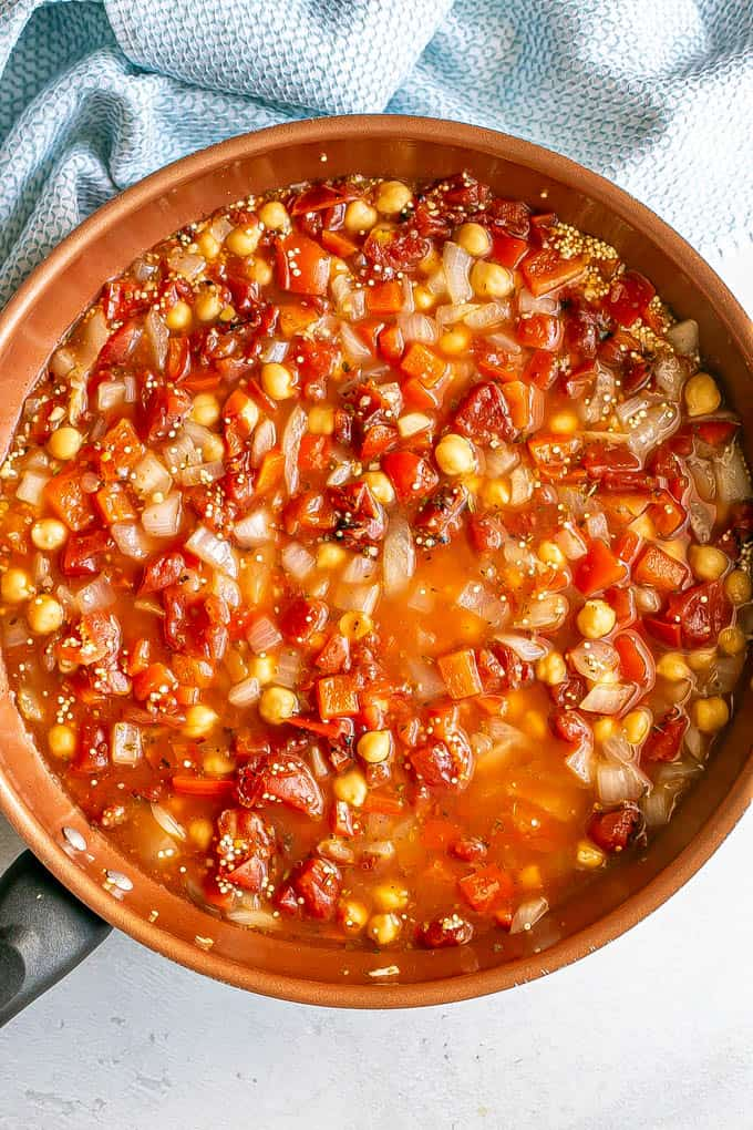 Quinoa, tomatoes and chickpeas in a large copper skillet