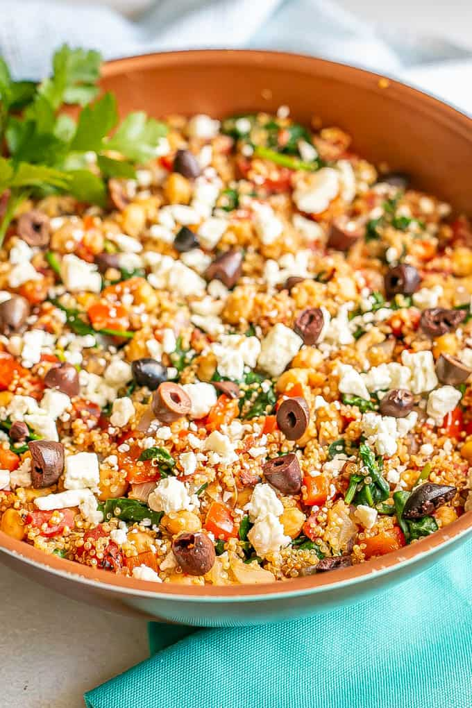 Quinoa and chickpea skillet with tomatoes and spinach with feta cheese on top