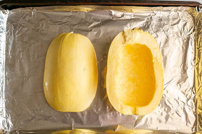 A halved spaghetti squash on a sheet pan before being baked