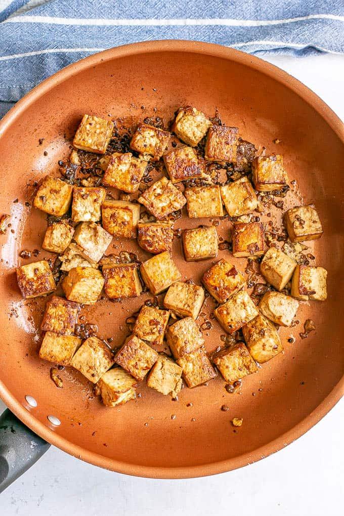 Crispy browned cubed tofu in a copper skillet