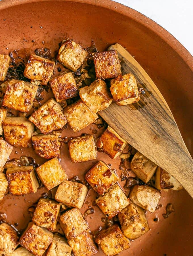Crispy browned cubed tofu in a copper skillet with a wooden spatula scooping some up