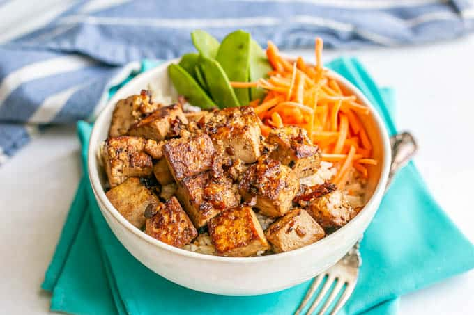Soy marinated crispy tofu in a white bowl with rice and veggies