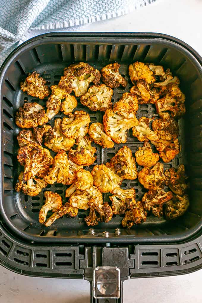 Cauliflower florets in the tray of an Air Fryer after being cooked
