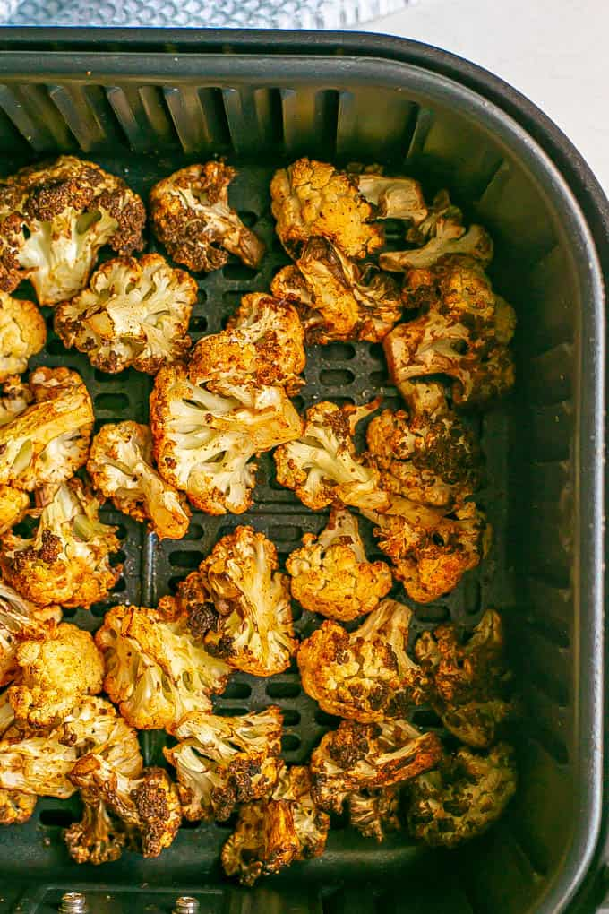Seasoned, crispy Air Fryer cauliflower florets in the tray after cooking