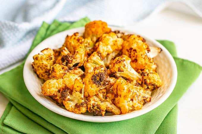 Browned, crispy cauliflower florets served in a white bowl set on green napkins