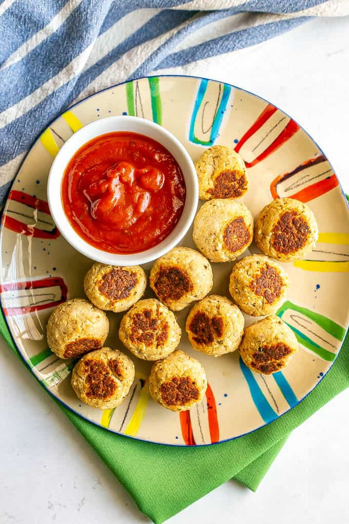A dozen small baby meatballs on a colorful plate with a little bowl of marinara sauce