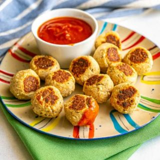 A dozen small baby meatballs on a colorful plate with a little bowl of marinara sauce and one meatball dipped in it