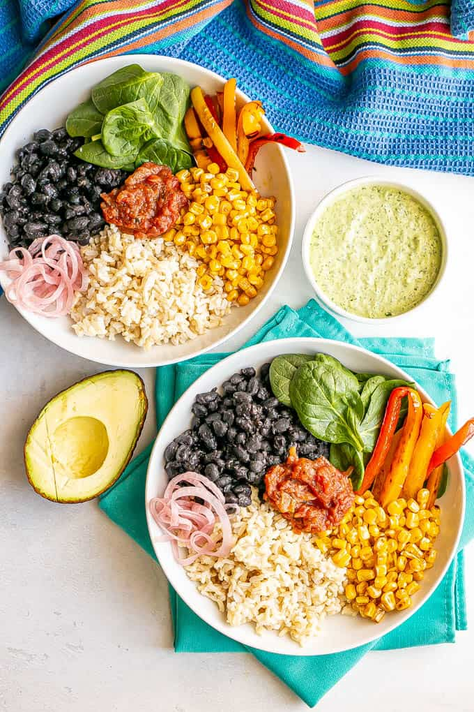 Two arranged bean and rice bowls with veggies and a half avocado and a bowl of green dressing nearby