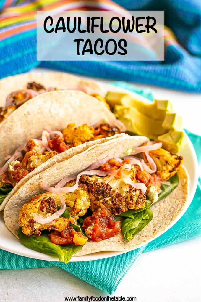 A trio of vegan cauliflower tacos in soft tortilla wraps on a white plate with spinach, salsa and red onions for toppings and a text overlay on the photo