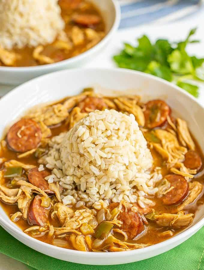 Chicken and sausage gumbo served in a wide low white bowl with a pile of rice in the middle