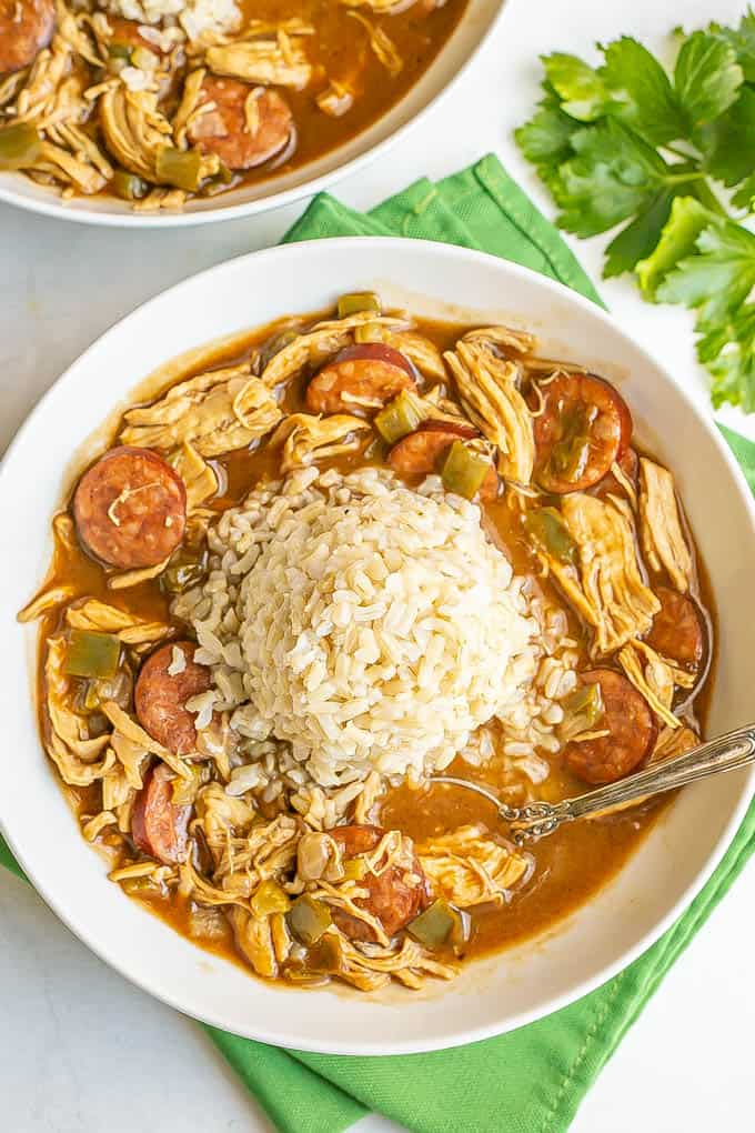 Chicken and sausage gumbo served in a wide low white bowl with a pile of rice in the middle and a spoon resting in the bowl