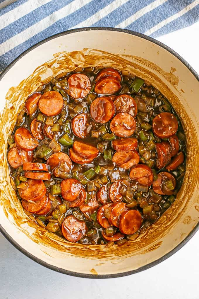 Andouille sausage with the trinity and a dark roux being cooked in a large pot