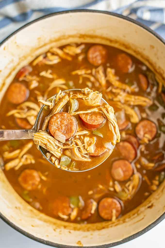 A ladle of gumbo being picked up from a large pot