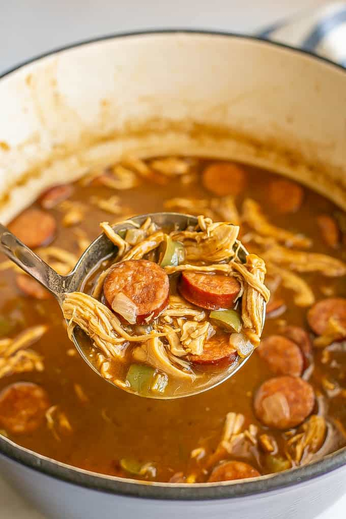 A ladle scooping up some chicken gumbo from a large purple pot