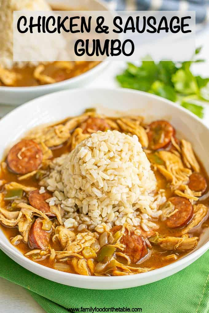 Chicken and sausage gumbo served in a wide low white bowl with a pile of rice in the middle and a text overlay on the photo