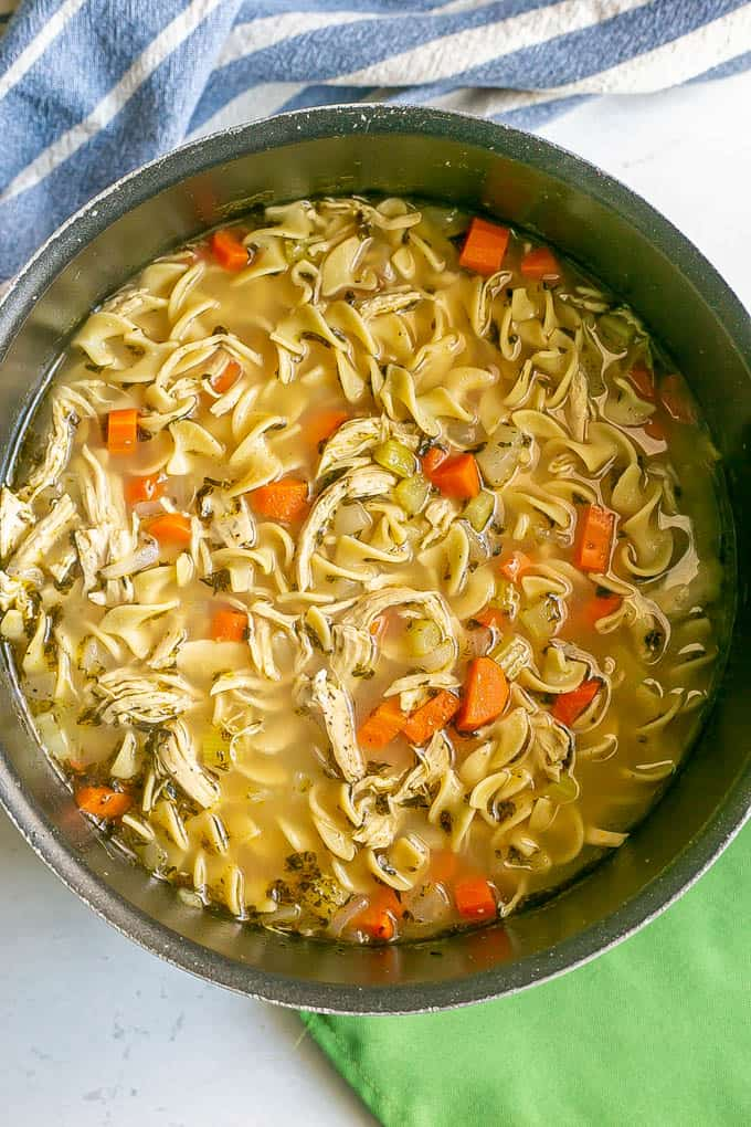 A large black pot filled with chicken noodle soup