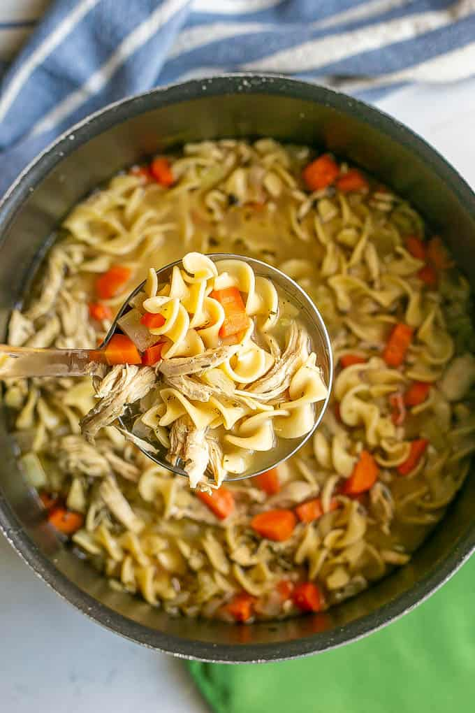 A ladle scooping some chicken noodle soup out of a large black pot to serve it