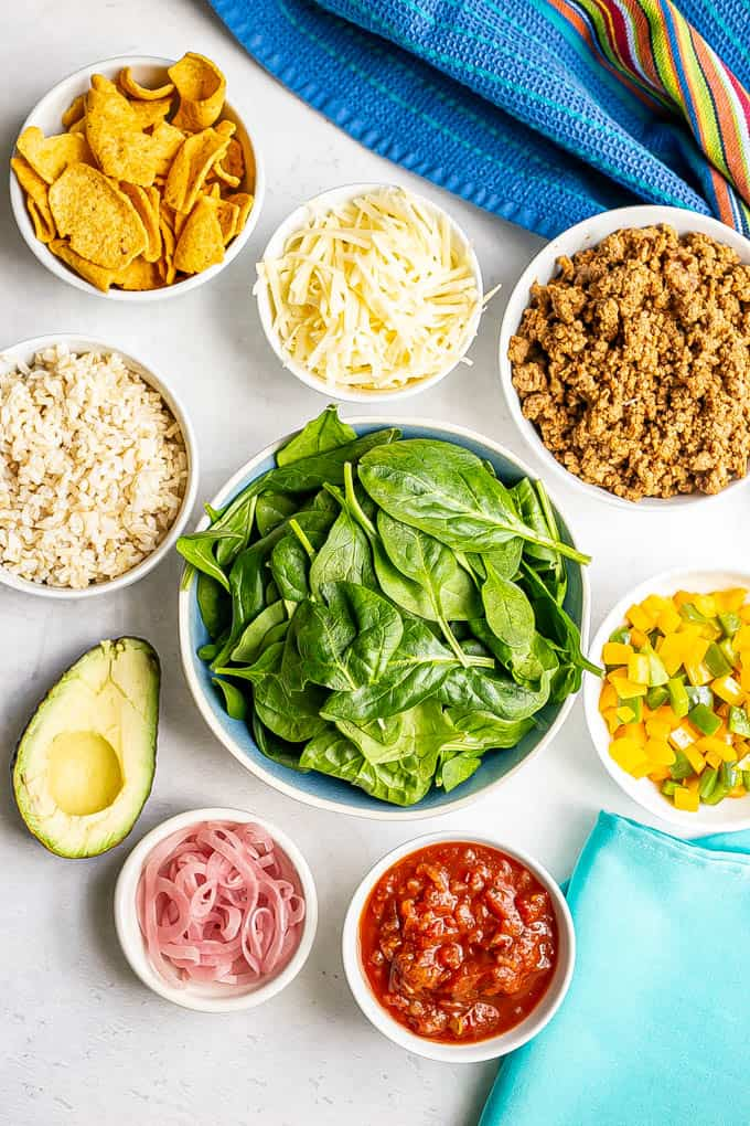 Bowls of ingredients laid out on a counter for building healthy taco salad bowls