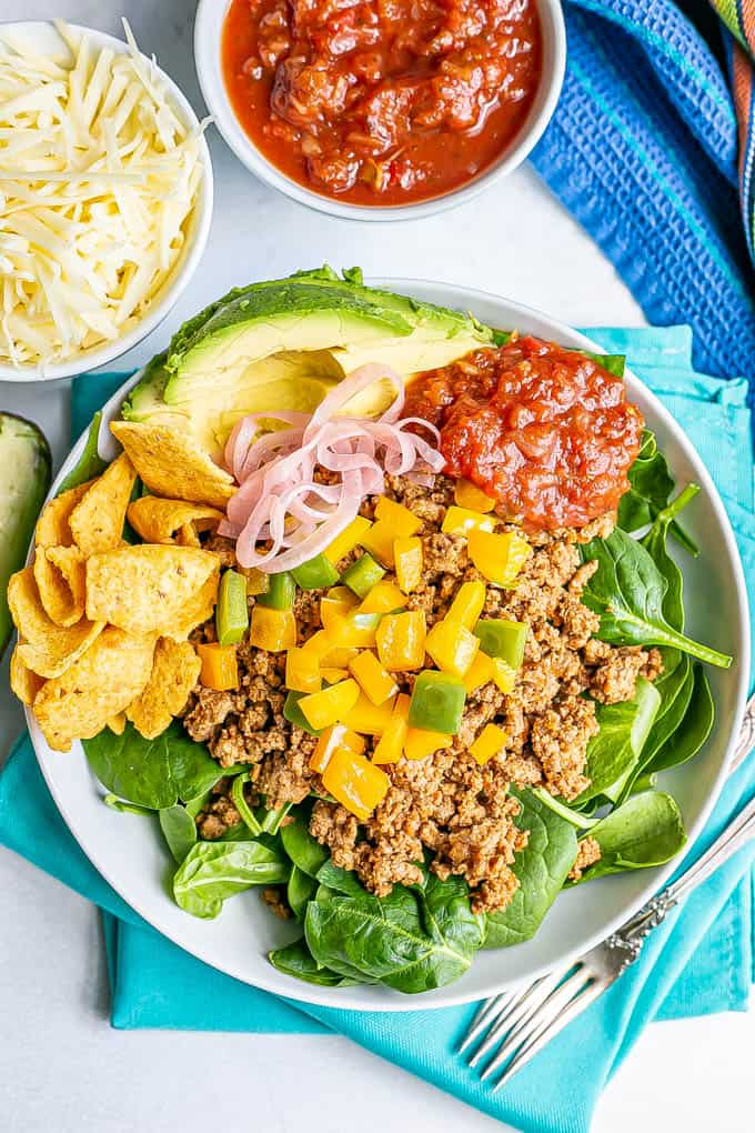 Ground turkey taco meat with bell peppers over fresh spinach in a white serving bowl with toppings of salsa, avocado and chips on the side
