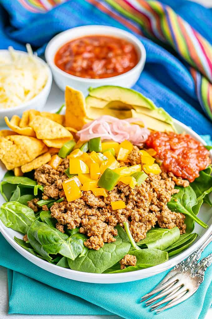 Ground taco meat with peppers piled on a bed of lettuce in a large shallow white bowl with toppings to the side