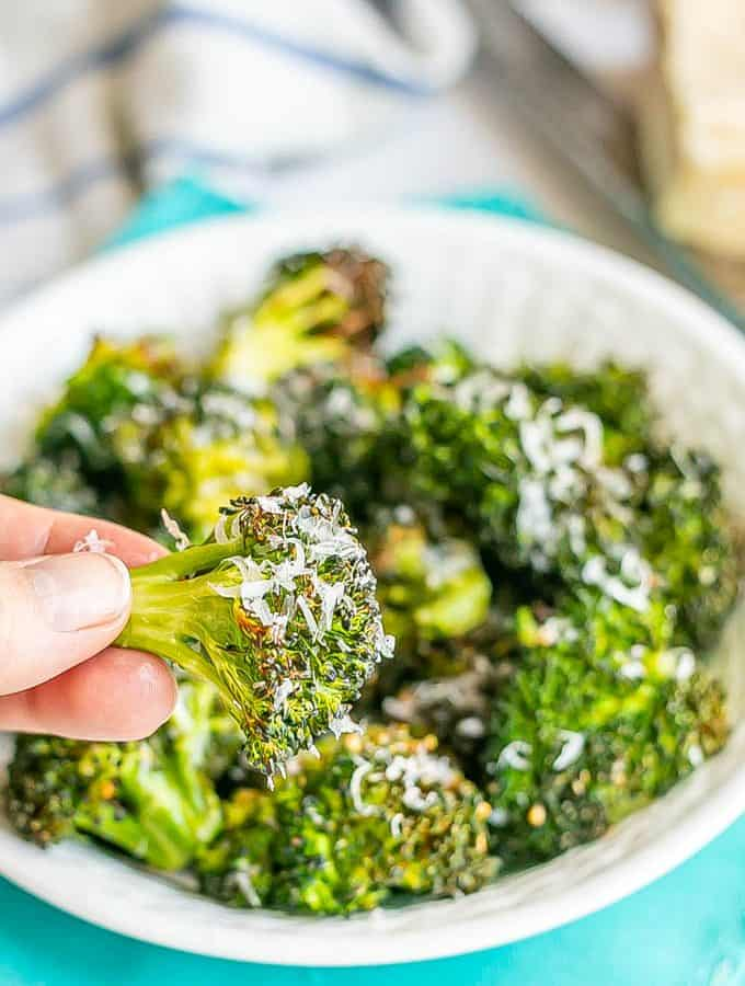A hand holding a crispy Air Fryer broccoli floret with Parmesan cheese grated on it