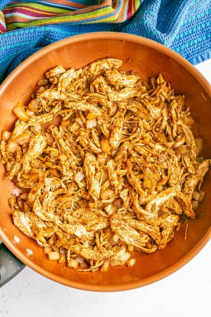 A large skillet with taco seasoned shredded chicken