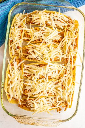 A casserole dish with chicken and cheese stuffed taco shells before being baked
