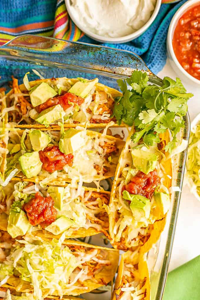 Crispy taco shells baked in a casserole dish and stuffed with shredded chicken, rice, refried beans and toppings