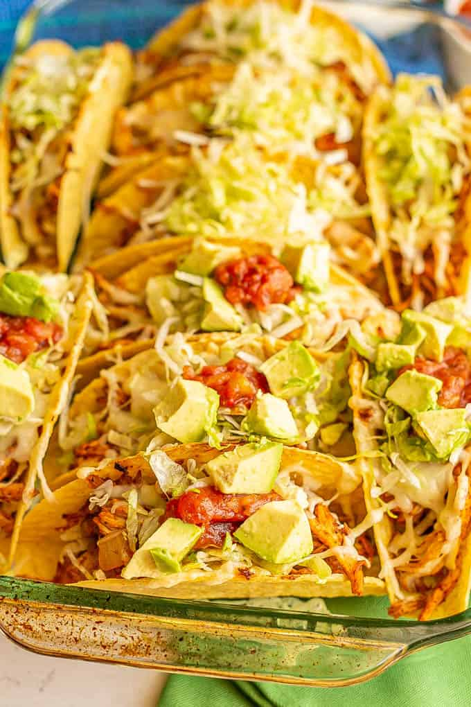 A glass casserole pan filled with crispy taco shells stuffed with chicken, rice and toppings
