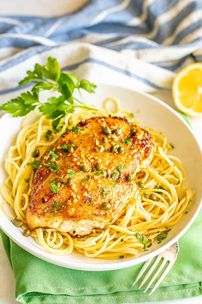 Chicken piccata served over thin spaghetti noodles in a low shallow white bowl with parsley sprinkled on top