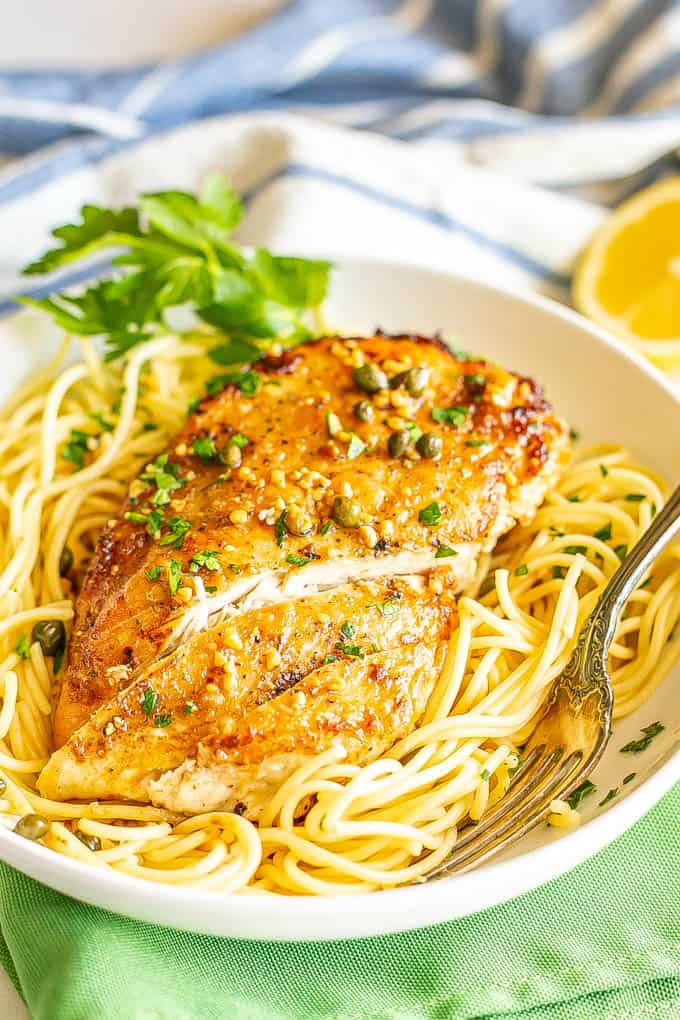 A thin, browned, sliced chicken breast served over spaghetti noodles with a sauce of capers, lemon and white wine