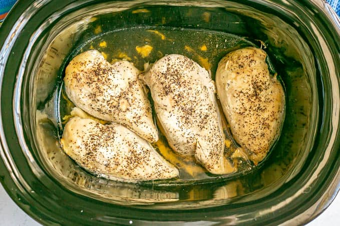 Seasoned, cooked chicken breasts in a slow cooker
