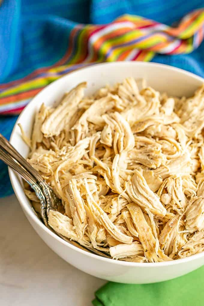 A large white bowl with shredded chicken and two forks tucked in the side, with colorful napkins on the table