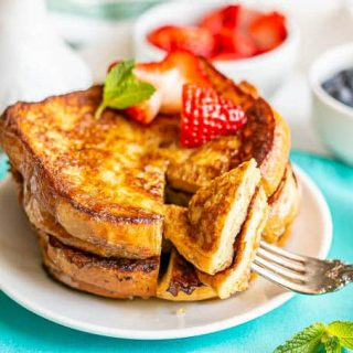 A fork picking up a cut out slice of French toast from a stack on a small white plate