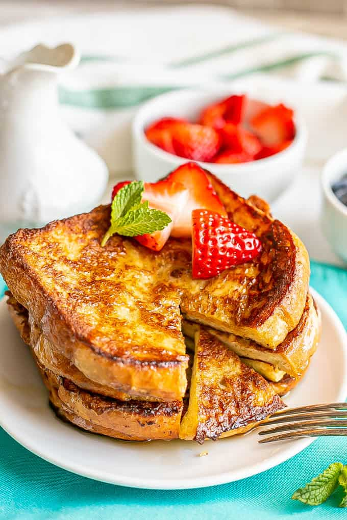 Stacked slices of French toast on a plate with berries on top and a small bite cut out