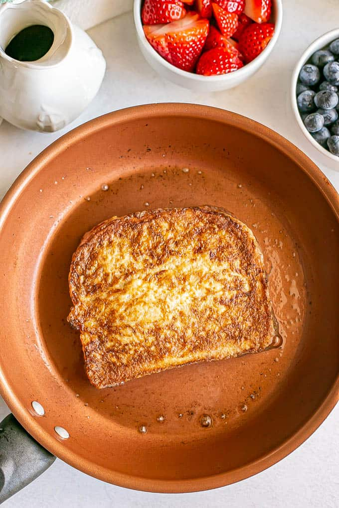 A slice of French toast being cooked in a copper skillet, with maple syrup and fresh berries on the counter nearby